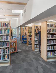 Pierson Library interior with volunteer shelving books in the adult non-fiction area